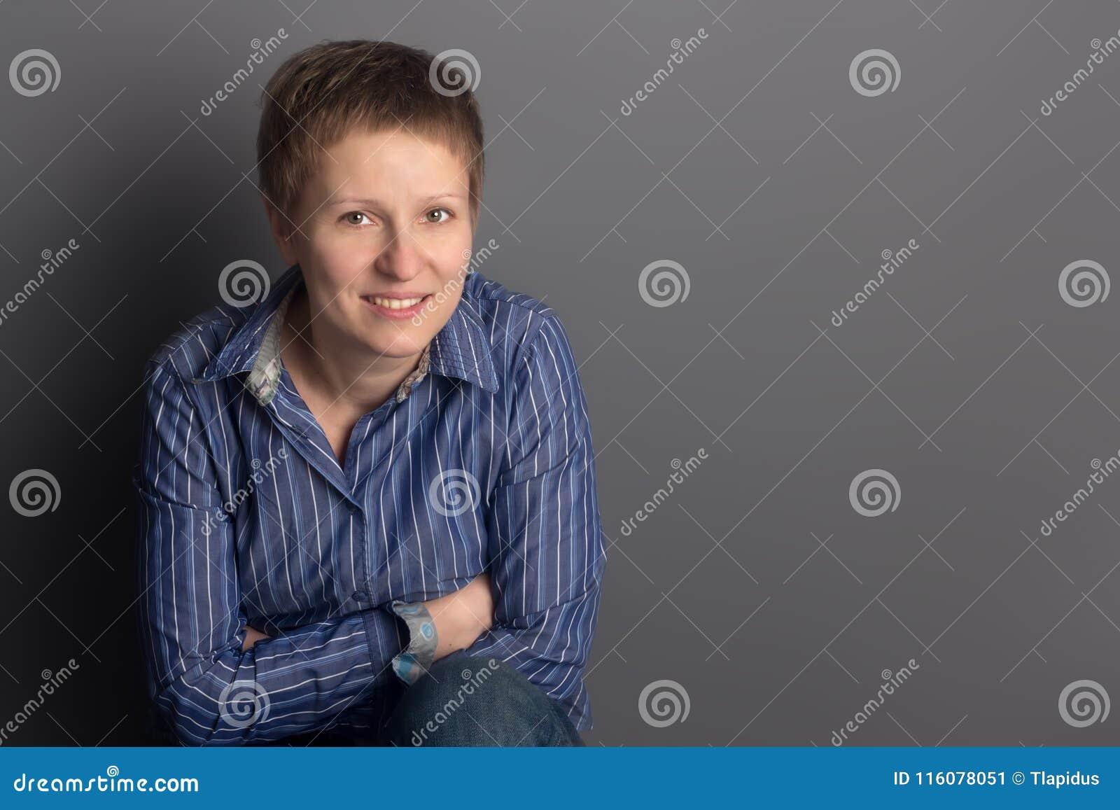 Gelukkige glimlachende vrouw op middelbare leeftijd in blauw overhemd