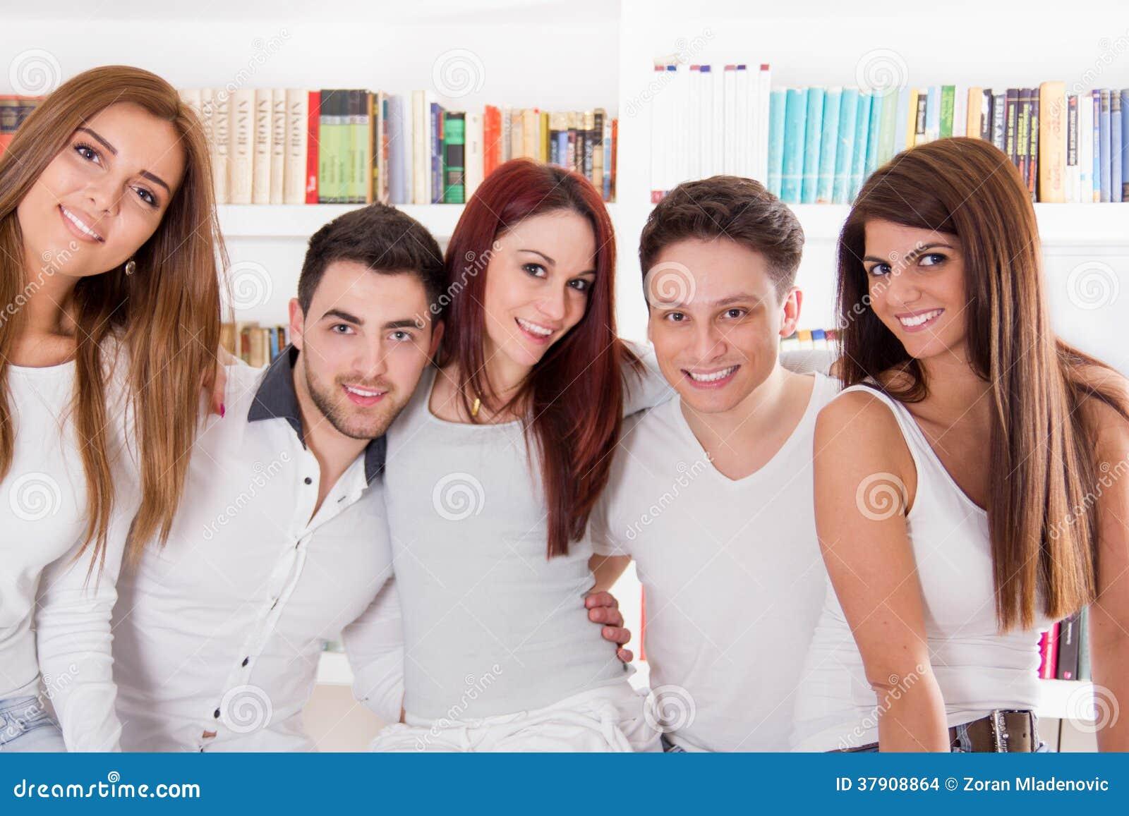 Gelukkige groep en vrienden die thuis glimlachen koesteren