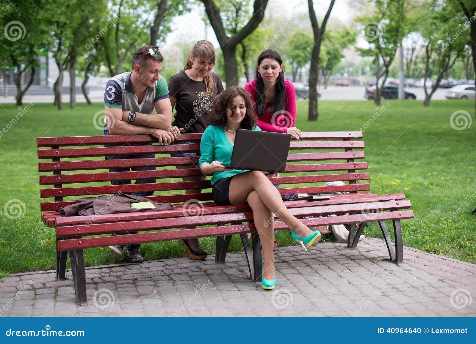 Gelukkige groep het jonge studenten zitten