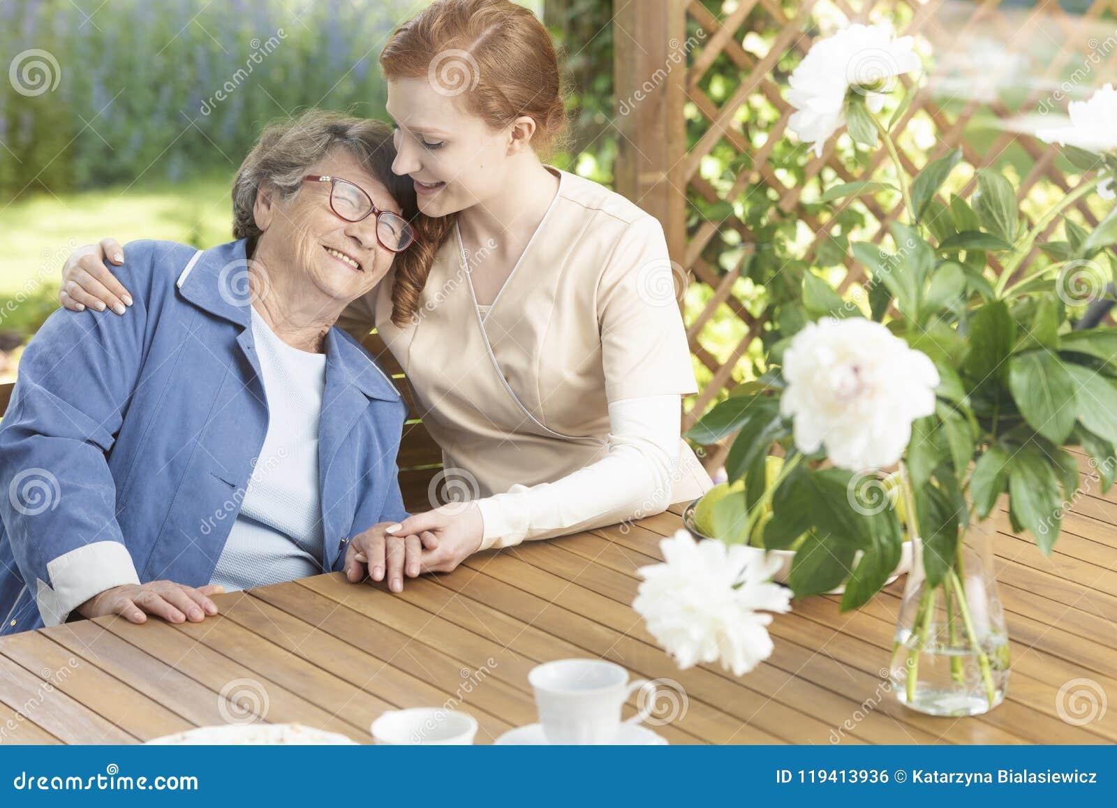 Gelukkige grootmoeder die van tijd met vriendschappelijke verpleegster op terra genieten