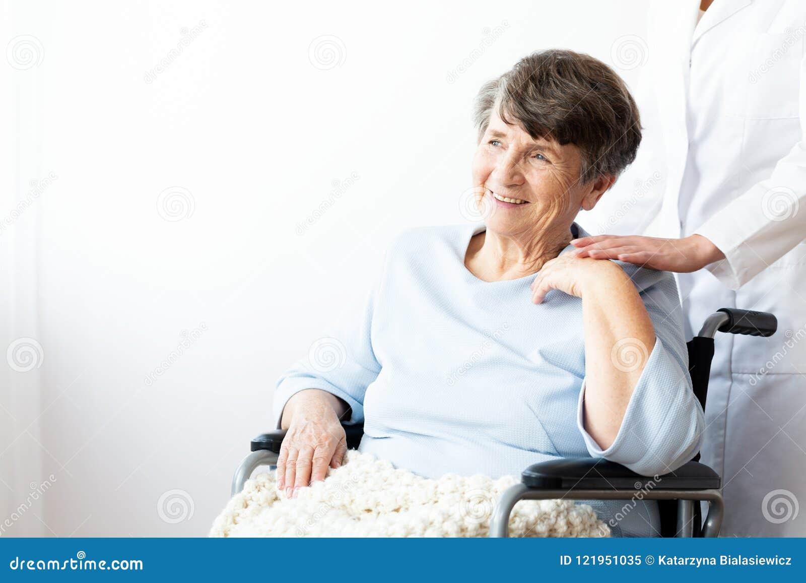 Gelukkige grootmoeder in een rolstoel en verzorger ondersteunend haar