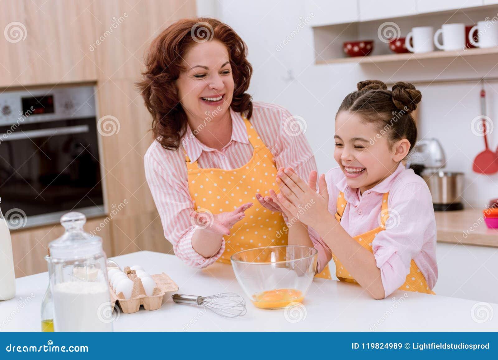 Gelukkige grootmoeder met weinig kleindochter die deeg voor het koken voorbereiden