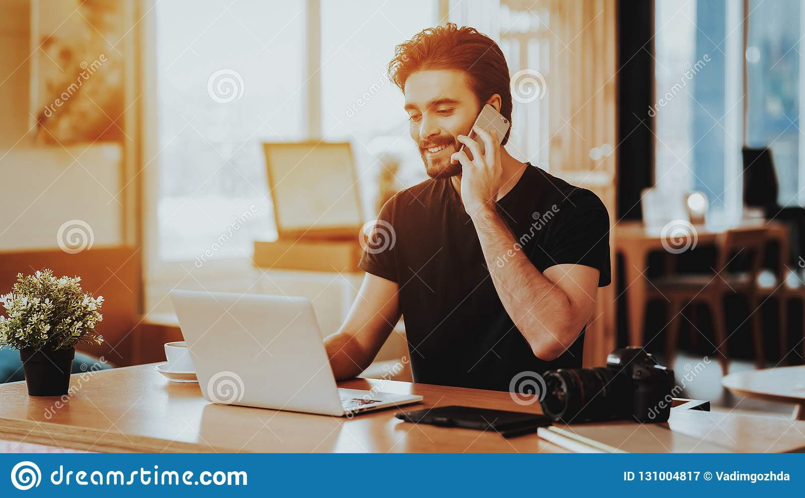 Gelukkige Guy Talks Phone en het Werk aangaande Laptop ver