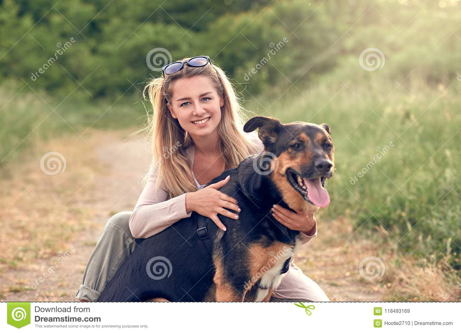 Gelukkige het glimlachen zwarte hond die een het lopen uitrustingszitting dragen die zijn vrij jonge vrouweneigenaar onder ogen z