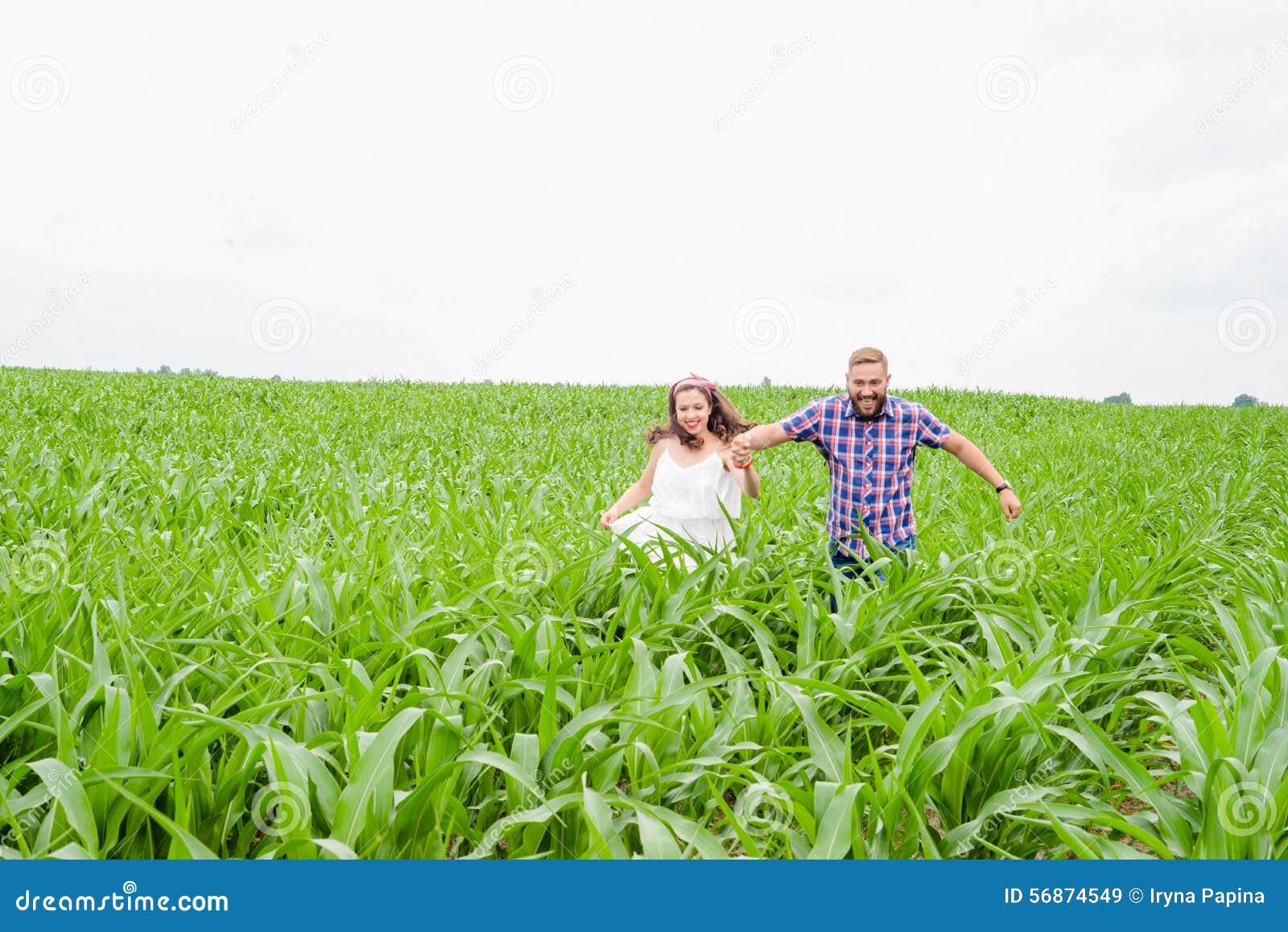 Gelukkige het houden van jonge volwassen paar het besteden tijd op het gebied op zonnige dag