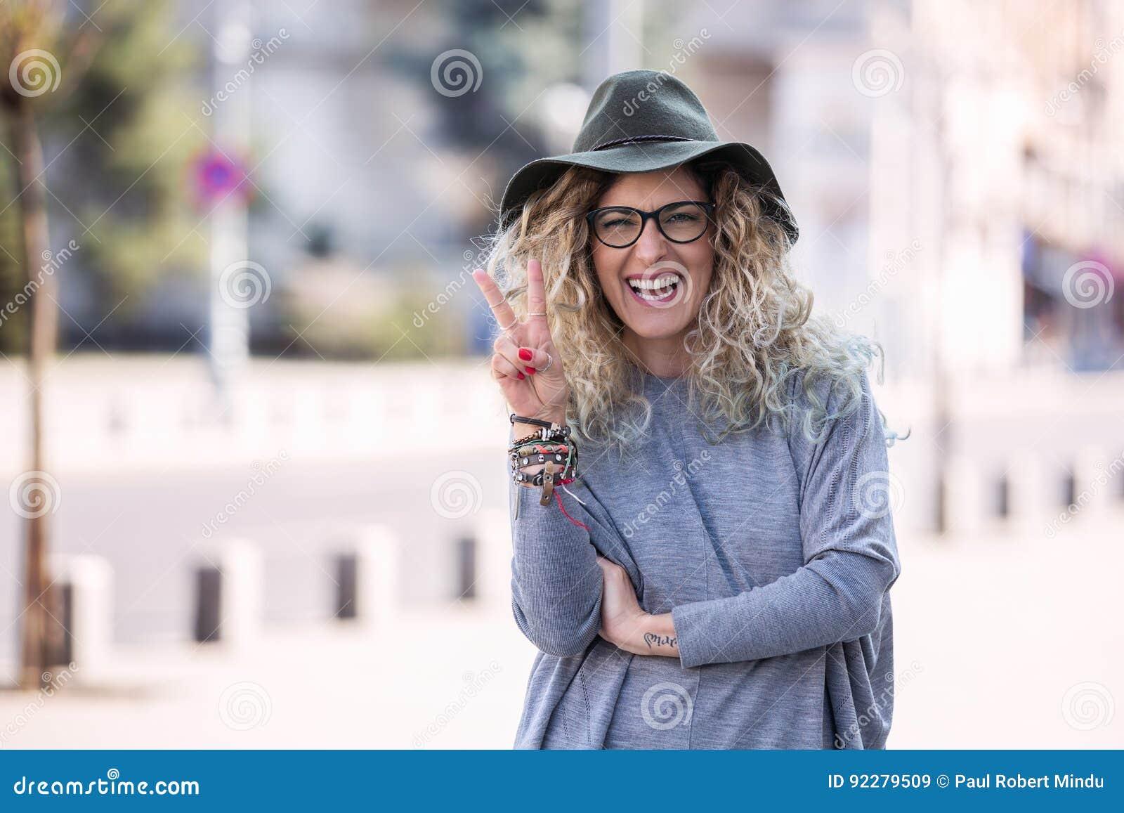 Gelukkige hipstervrouw die hoed en glazen in de stadszomer dragen