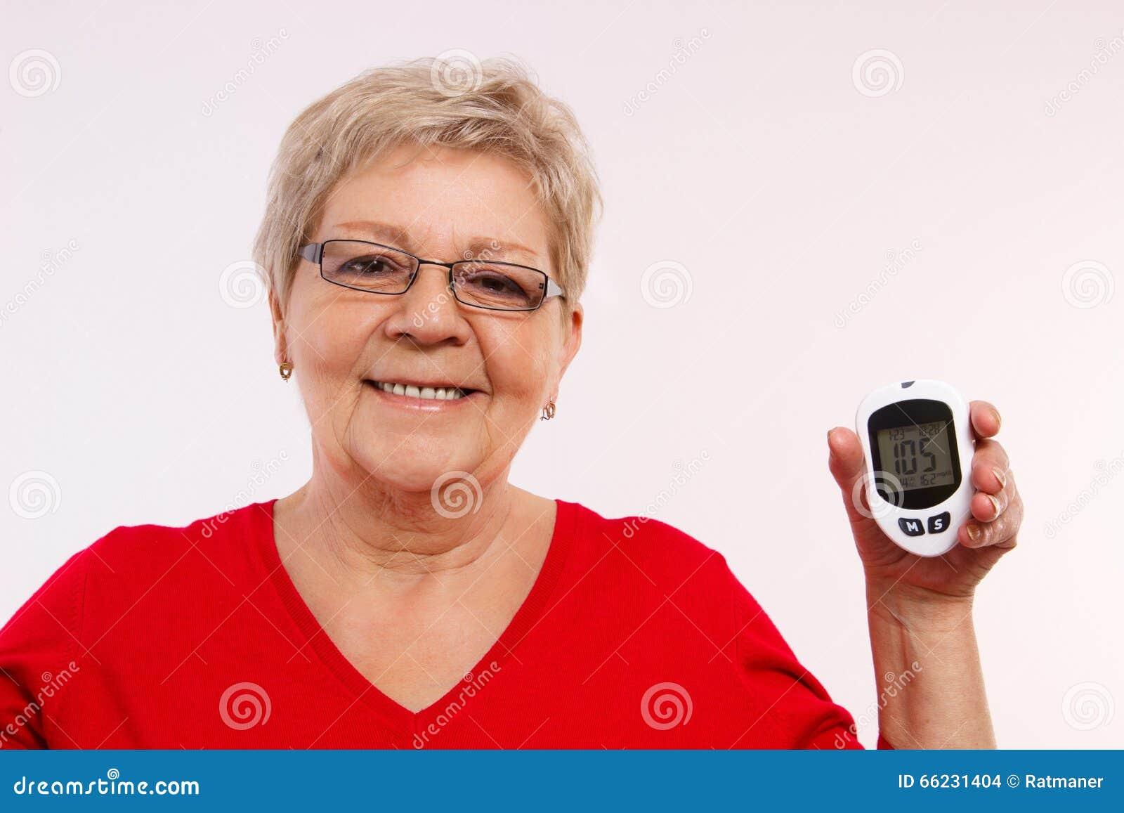 Gelukkige hogere glucometer die van de vrouwenholding, die en suikerniveau, concept meten controleren diabetes in oude dag