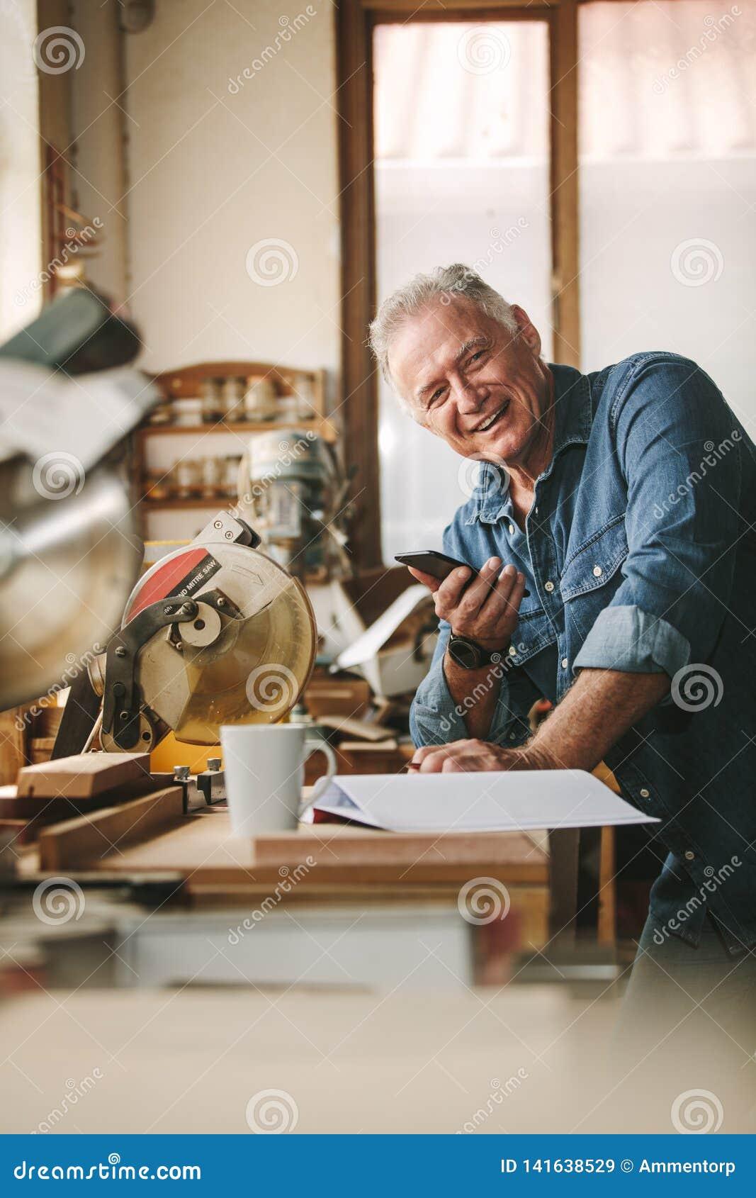 Gelukkige hogere mannelijke timmerman met telefoon in workshop