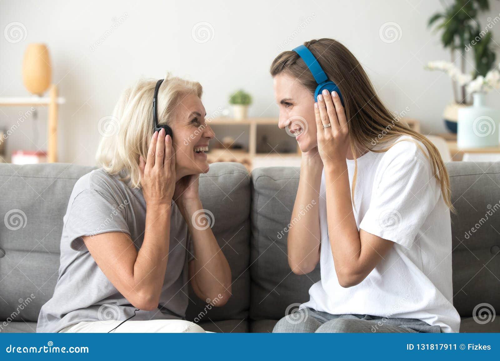 Gelukkige hogere moeder en volwassen dochter het luisteren muziek in headph