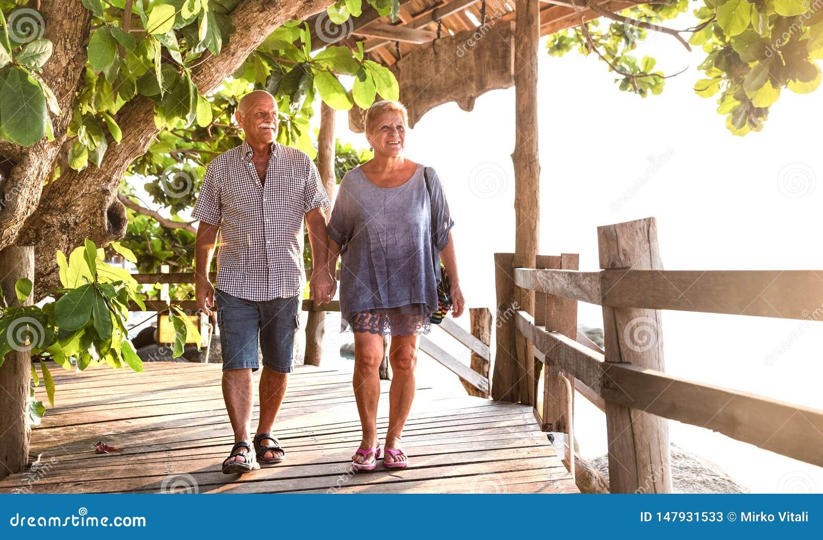 Gelukkige hogere paar het lopen holdingshand bij Koh Phangan-strandpromenade - Actieve bejaarden en het concept van de reislevens