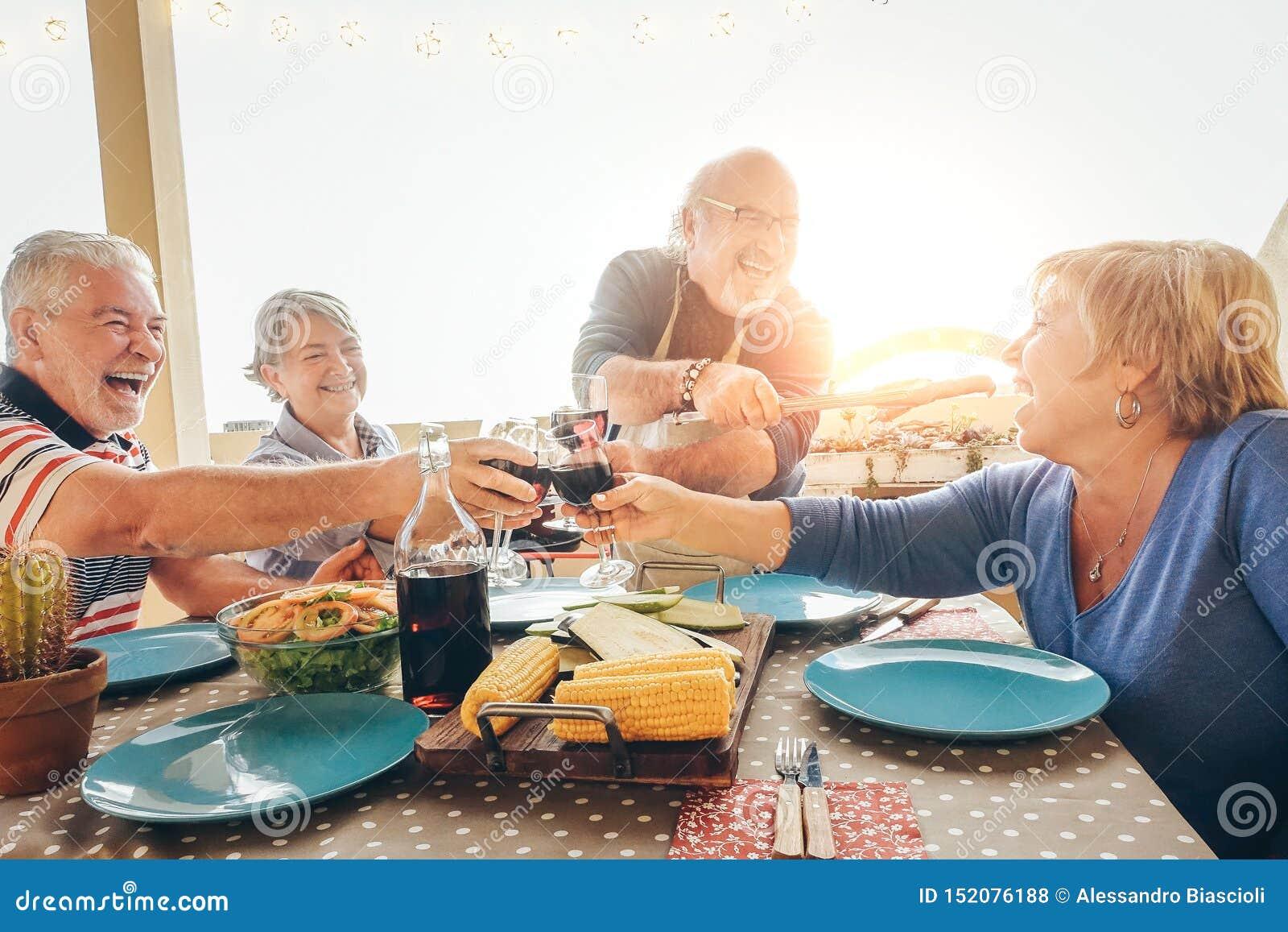 Gelukkige hogere vrienden die pret hebben die met rode wijn bij barbecue in terras toejuichen openlucht - Oudere mensen die met g