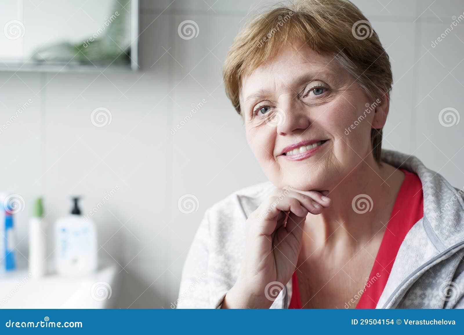 Gelukkige hogere vrouw in de badkamers