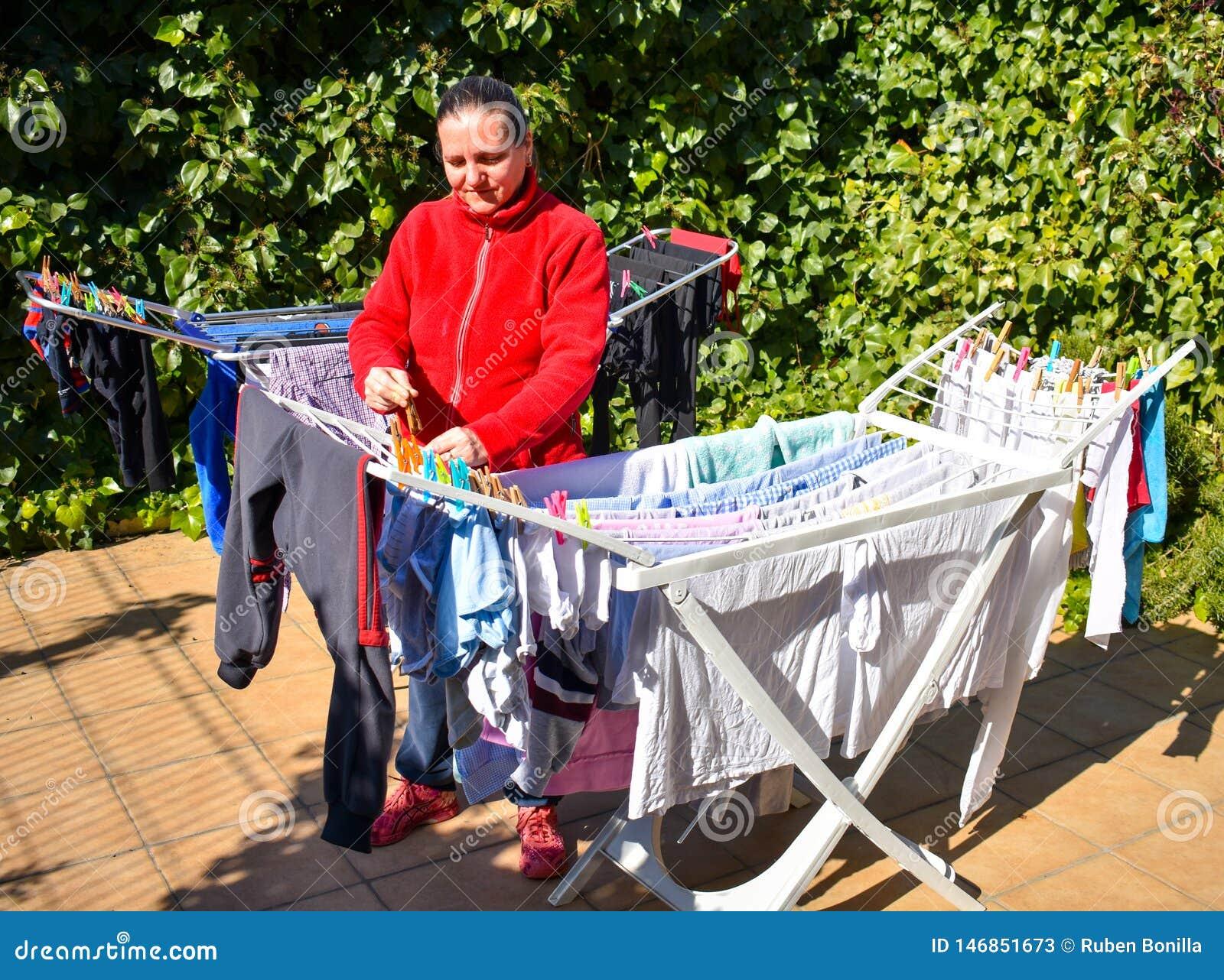 Gelukkige huisvrouw die de natte die kleren houden enkel uit de wasmachine in de waslijn gezet worden verwijderd op het terras va