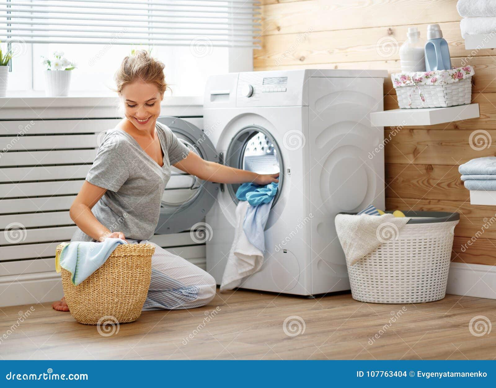 Gelukkige huisvrouwenvrouw in wasserijruimte met wasmachine