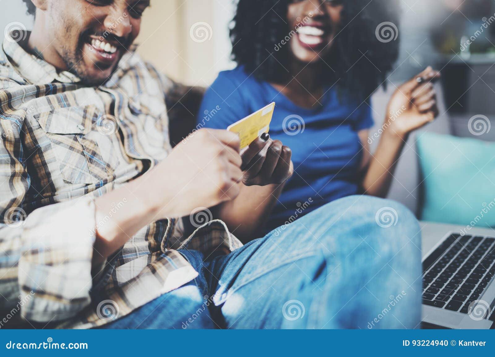 Gelukkige jonge Afrikaanse Amerikaanse paarzitting op bank thuis en online winkelend door mobiele computer door creditcard