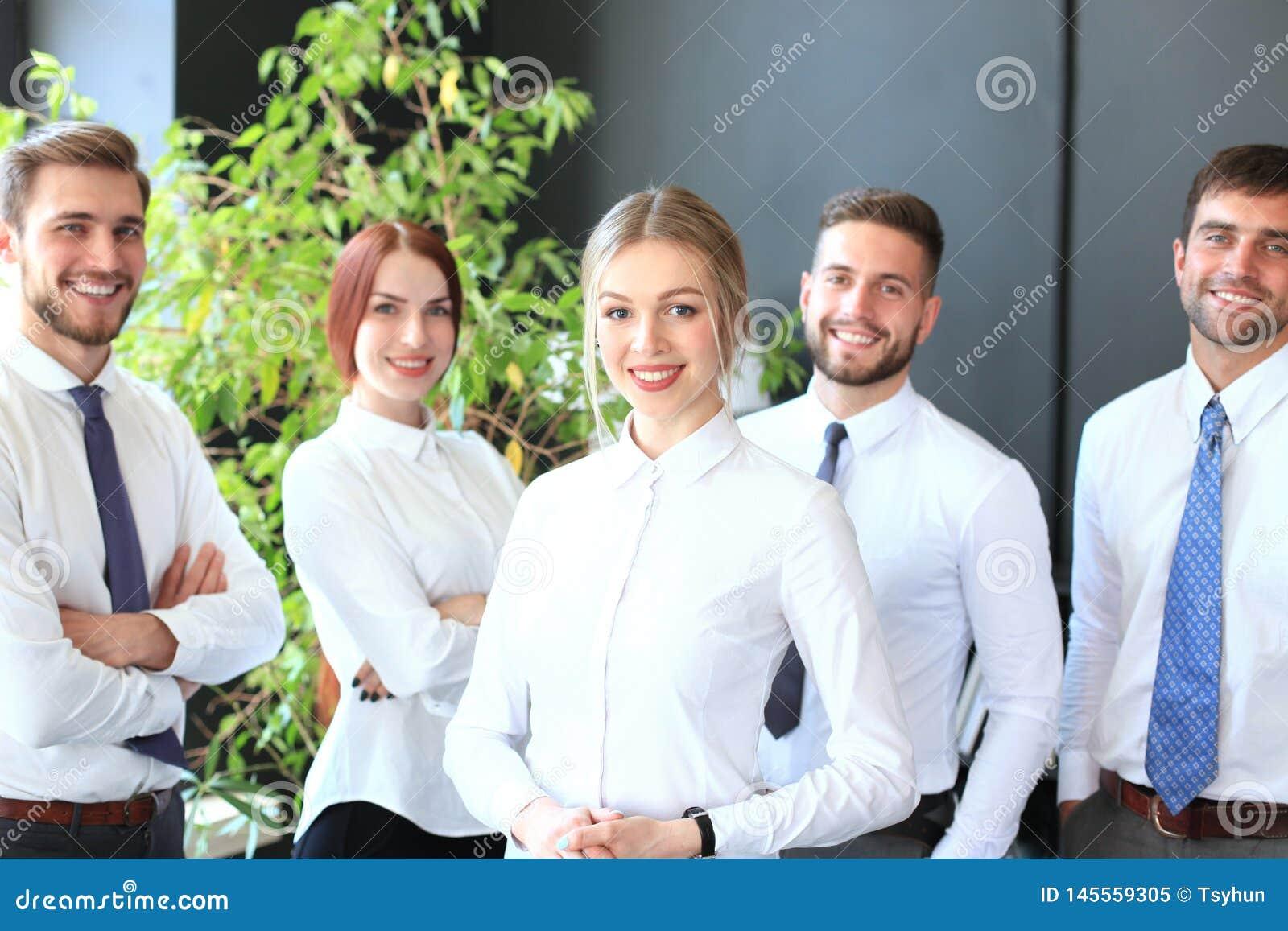 Gelukkige jonge bedrijfsvrouw die zich voor haar team bevinden