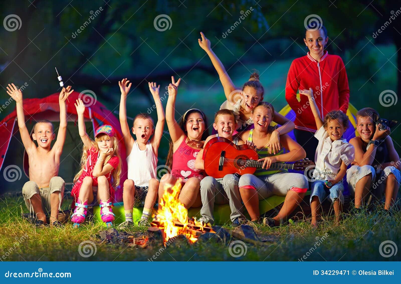 Gelukkige jonge geitjes die liederen zingen rond kampbrand