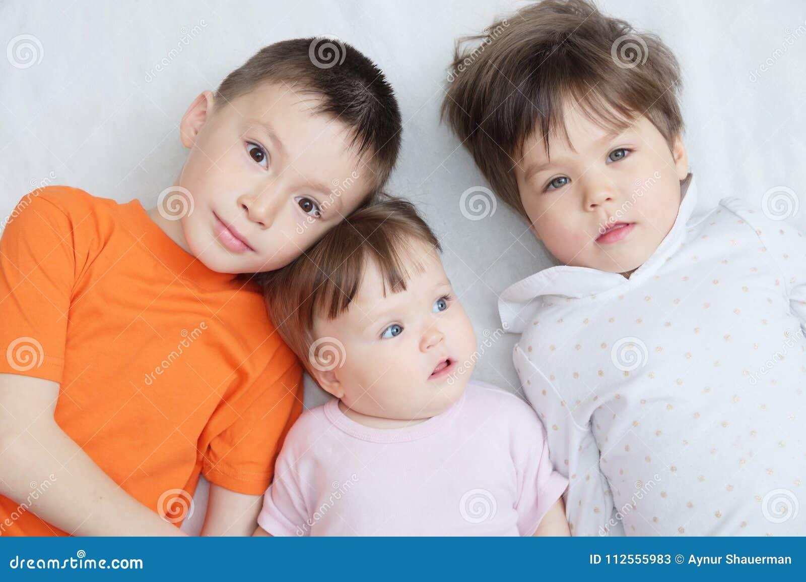 Gelukkige jonge geitjes, drie kinderen verschillende leeftijden, portret van jongen, meisje en babymeisje, geluk die in kinderjar