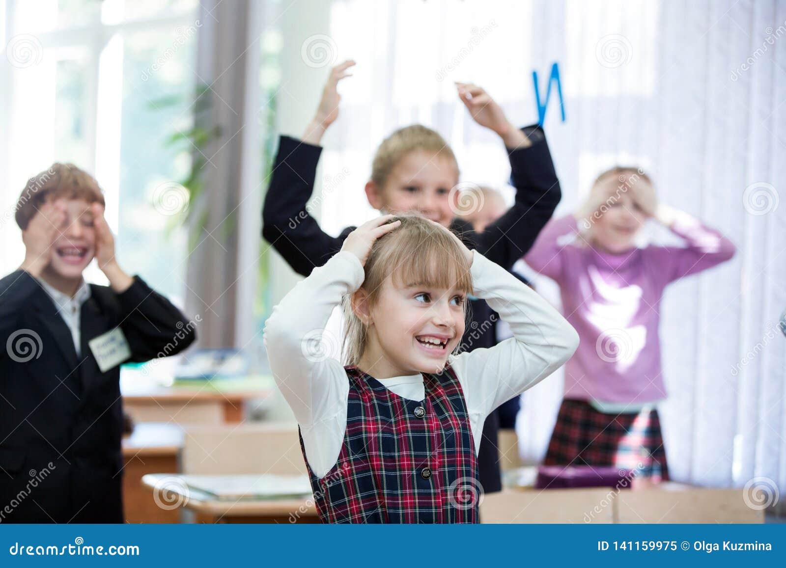 Gelukkige jonge geitjes in schoolklasse De kinderen hebben het doen van oefeningen Lage school