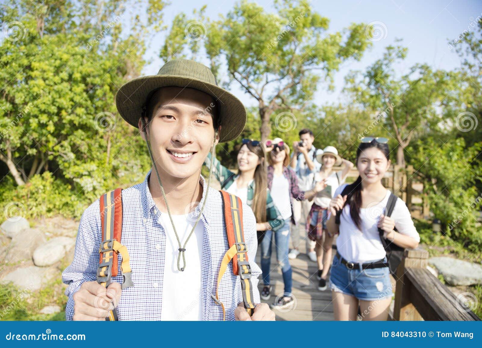 Gelukkige jonge groep die samen door het bos wandelen