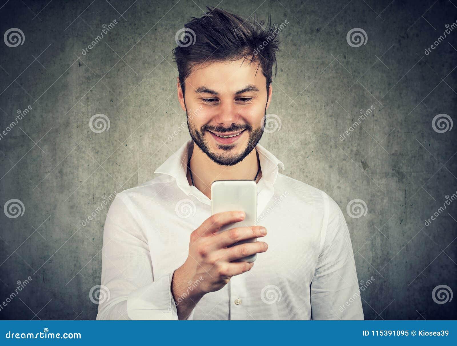 Gelukkige jonge kerel het letten op smartphone
