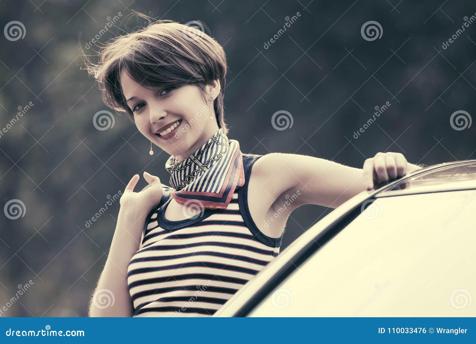 Gelukkige jonge maniervrouw in gestreept mouwloos onderhemd die op haar auto leunen