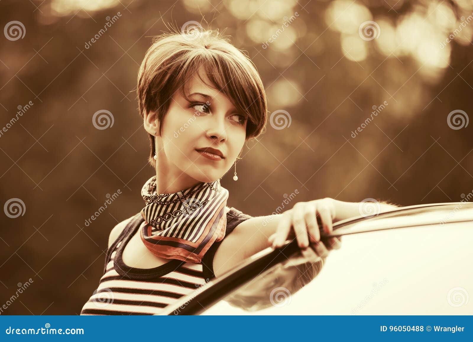 Gelukkige jonge maniervrouw in mouwloos onderhemd naast haar auto