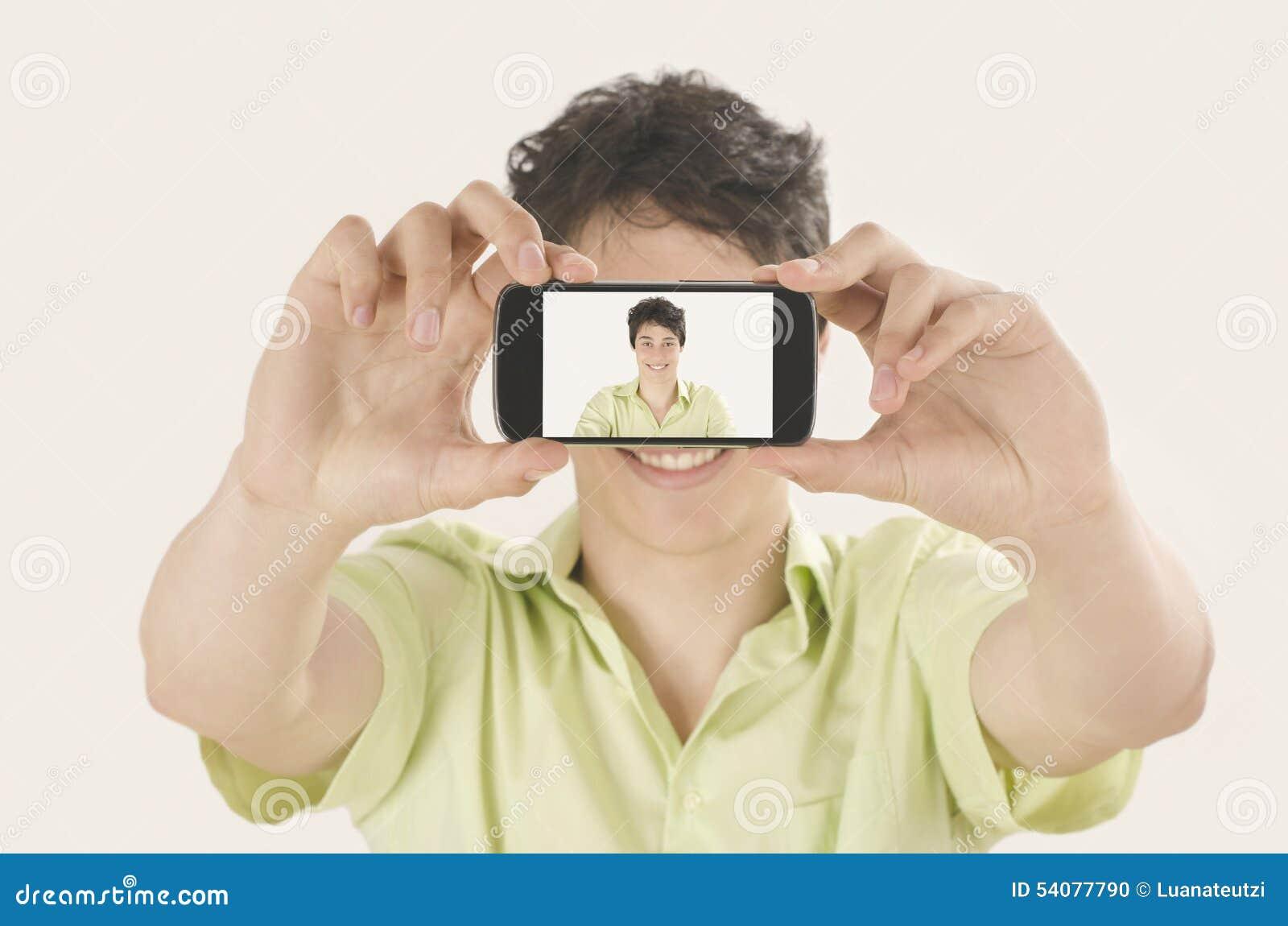 Gelukkige jonge mens die een selfiefoto met zijn slimme telefoon nemen