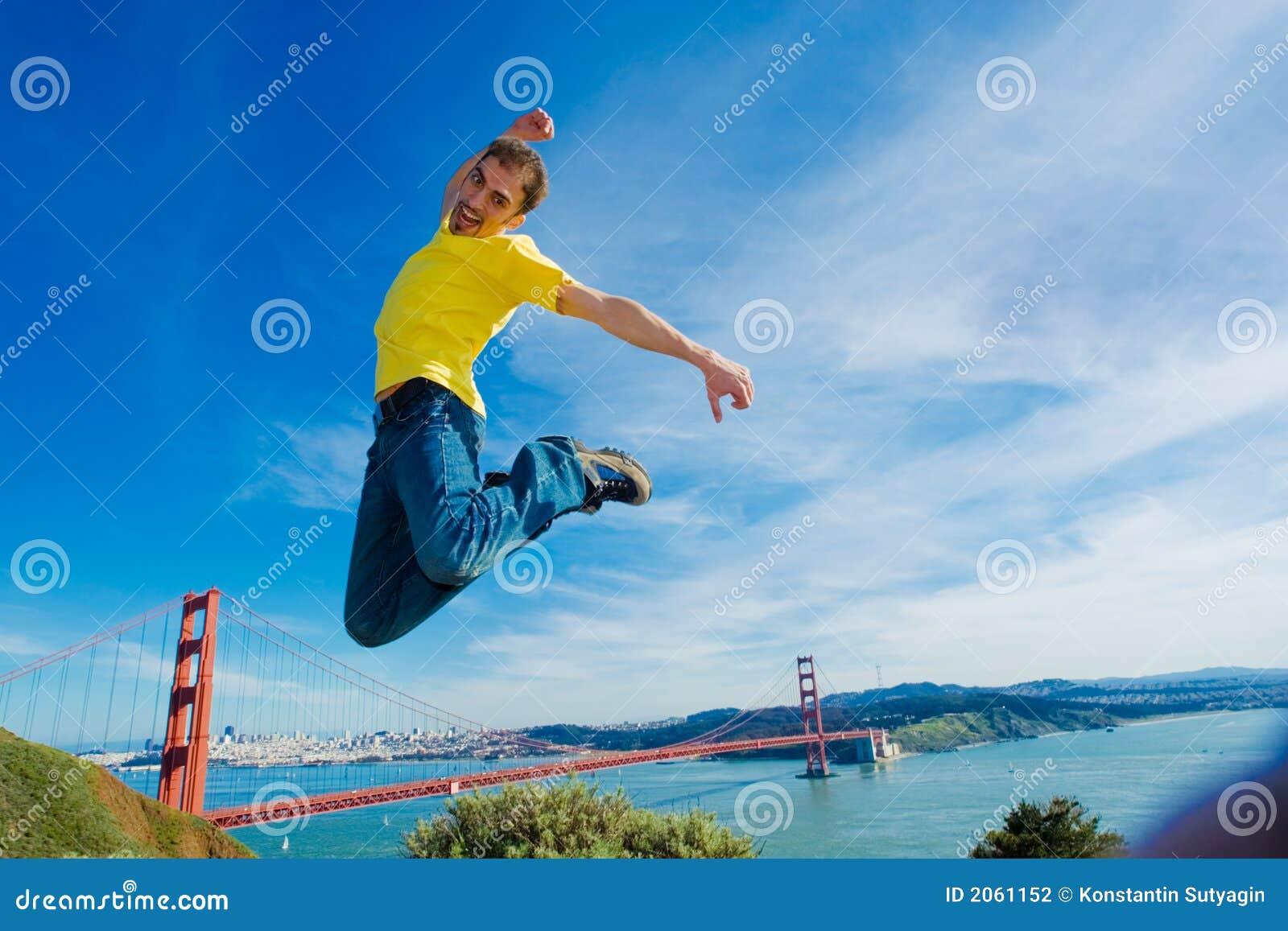 Gelukkige jonge mens die hoog in de lucht springt