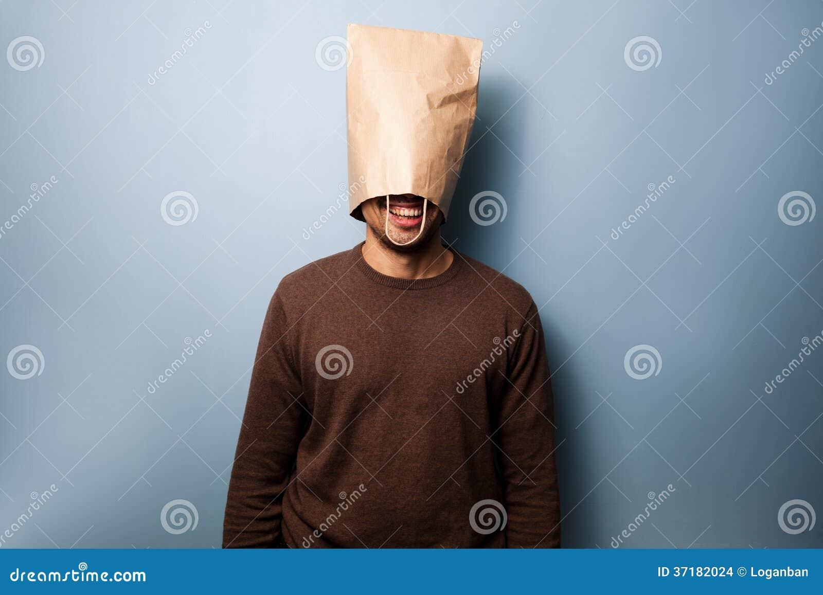 Gelukkige jonge mens met een zak over zijn hoofd