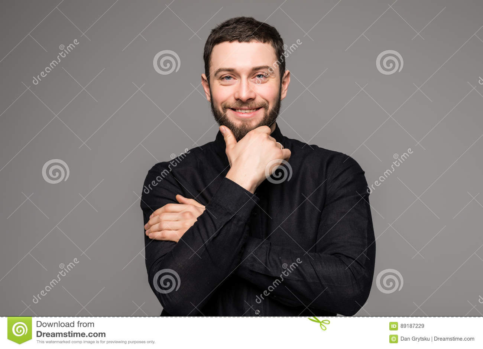 Gelukkige jonge mens Portret van de knappe jonge mens die in toevallig overhemd terwijl status tegen grijze achtergrond glimlache