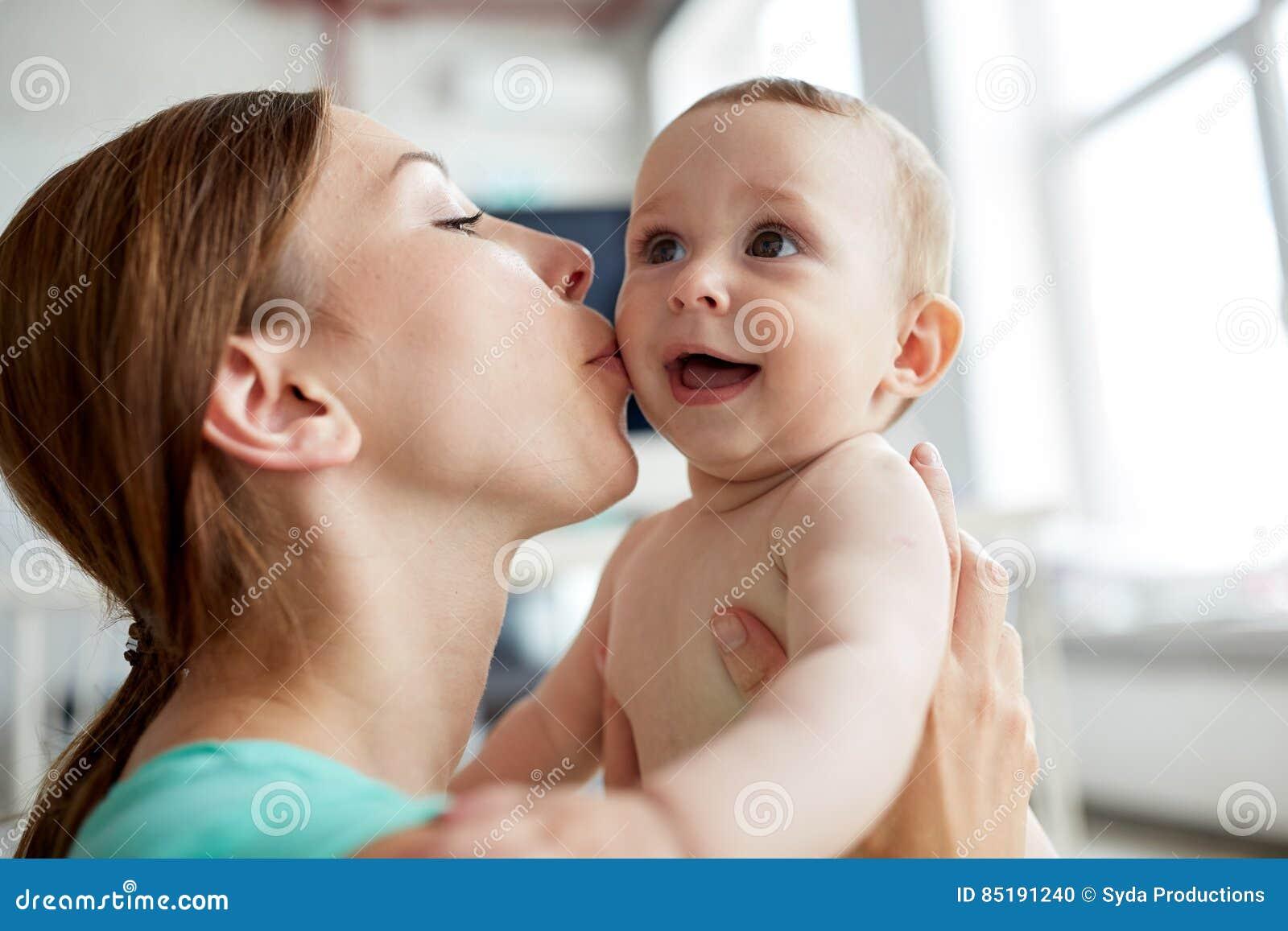 Gelukkige jonge moeder die weinig baby thuis kussen