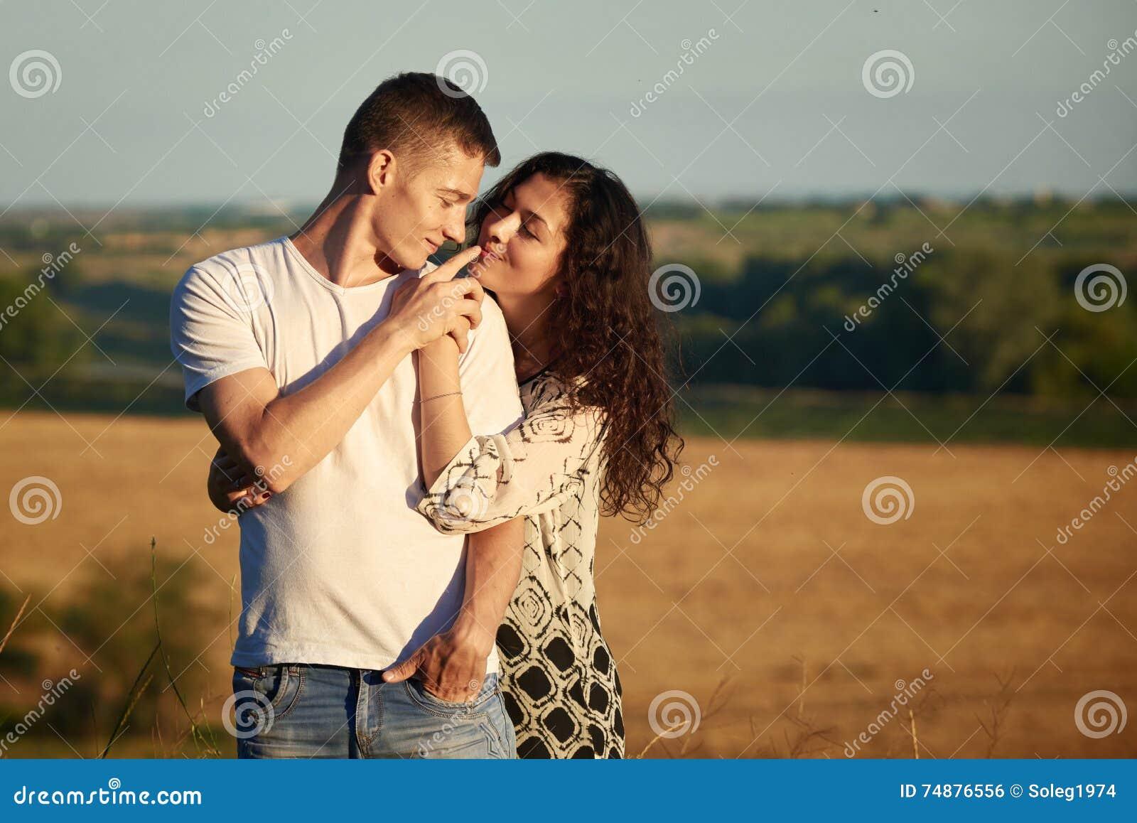 Gelukkige jonge paar stellende hoogte op land openlucht over geel gebied, romantisch mensenconcept, zomer