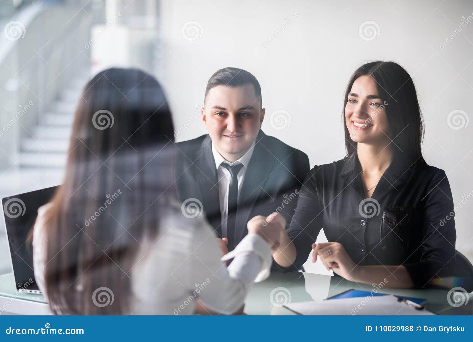 Gelukkige jonge paarvergadering met een makelaar in haar bureau die over het bureau aan schokhanden leunen, mening van achter de