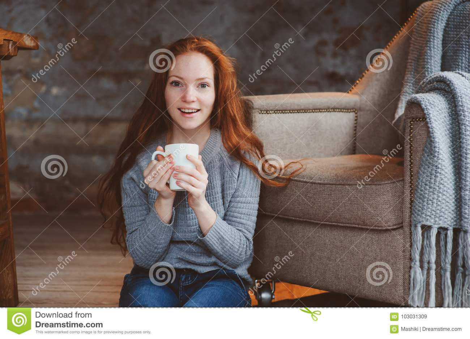 Gelukkige jonge readheadvrouw die hete koffie of thee thuis drinken Kalm en comfortabel weekend in de winter