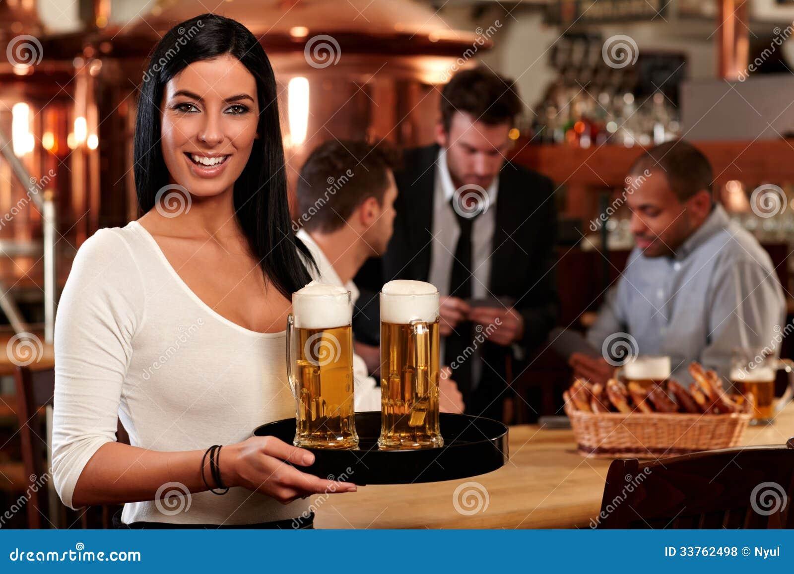 Gelukkige jonge serveerster met bier