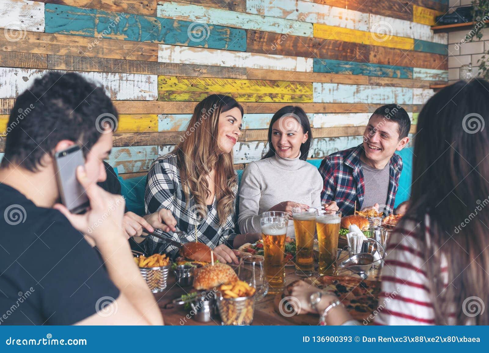 Gelukkige jonge vrienden die met pizzaburgers en het drinken bier bij barrestaurant vieren