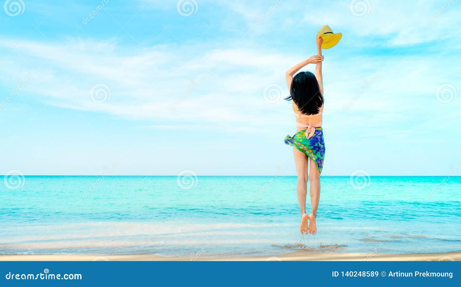 Gelukkige jonge vrouw in de roze swimwear hoed van de handholding en het springen bij zandstrand Het ontspannen van en het geniet