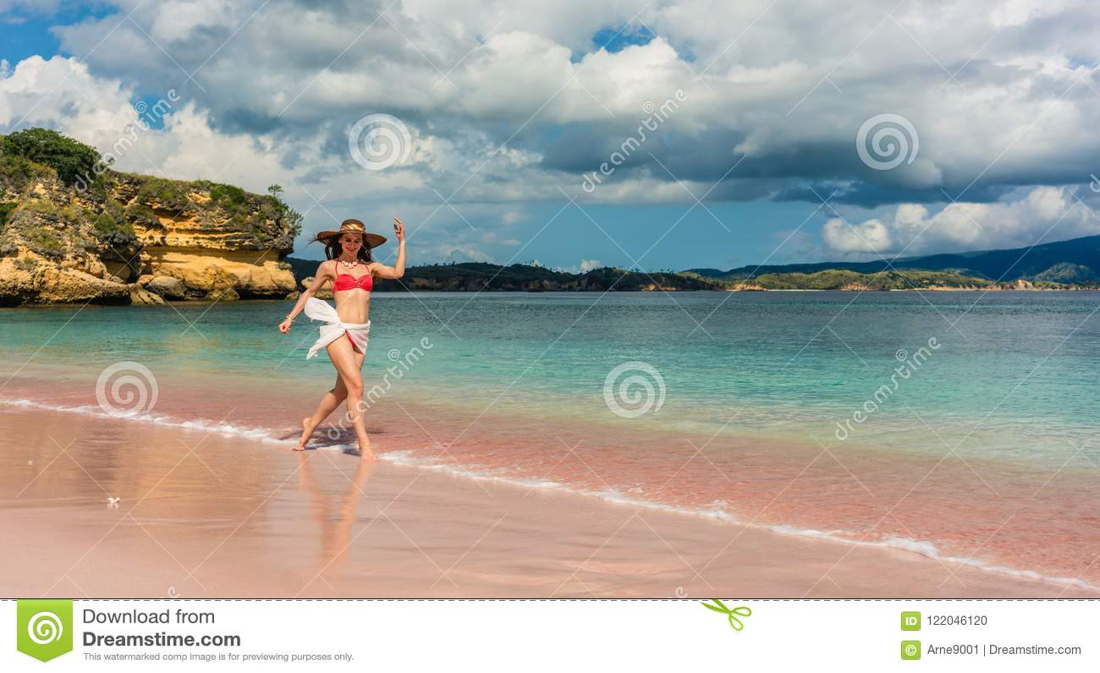 Gelukkige jonge vrouw die door ondiep zeewater op het strand lopen