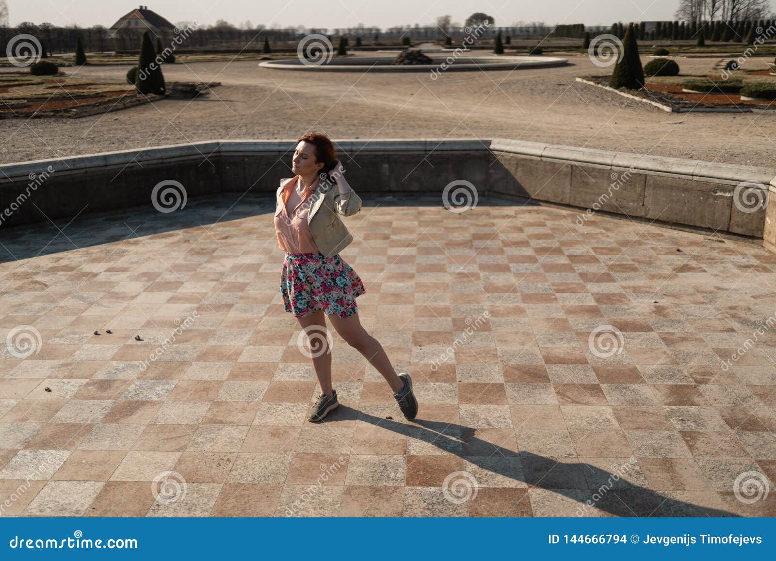 Gelukkige jonge vrouw die in een lege fontein danst die een kleurrijke rok draagt