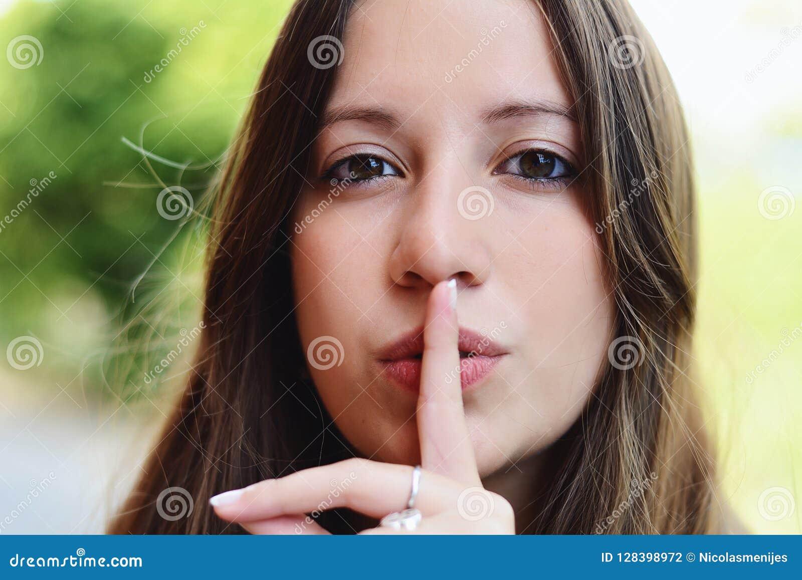 Gelukkige jonge vrouw die een stil gebaar maken
