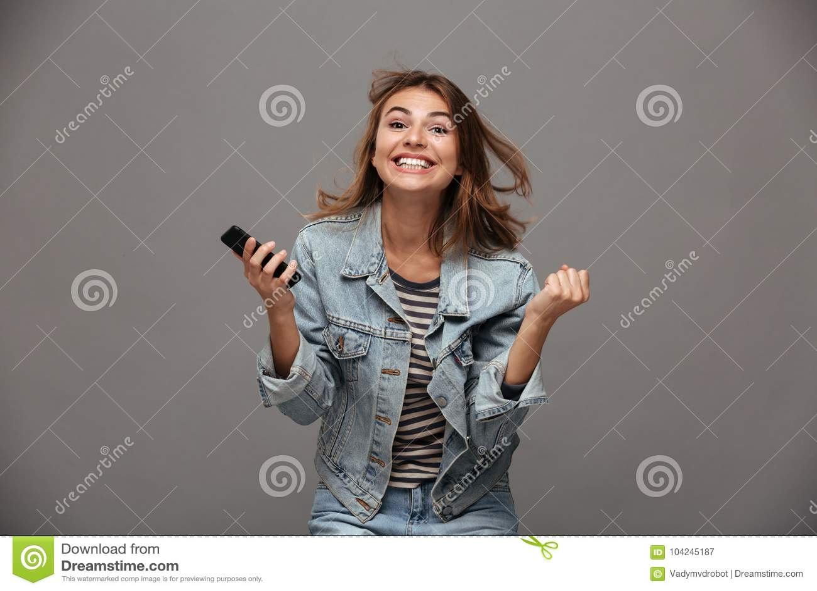 Gelukkige jonge vrouw die in jeansjasje haar vuisten in winnaar dichtklemmen