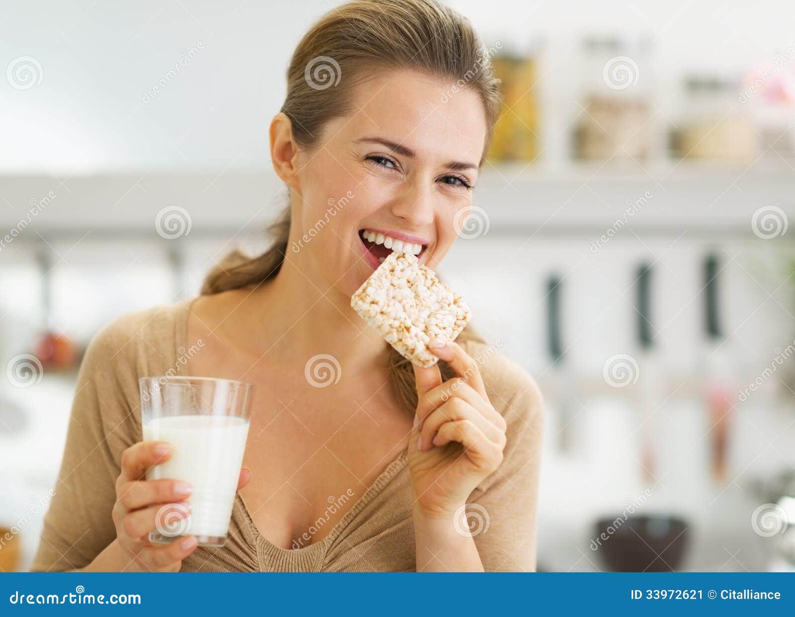Gelukkige jonge vrouw die kernachtig brood met melk in keuken eten