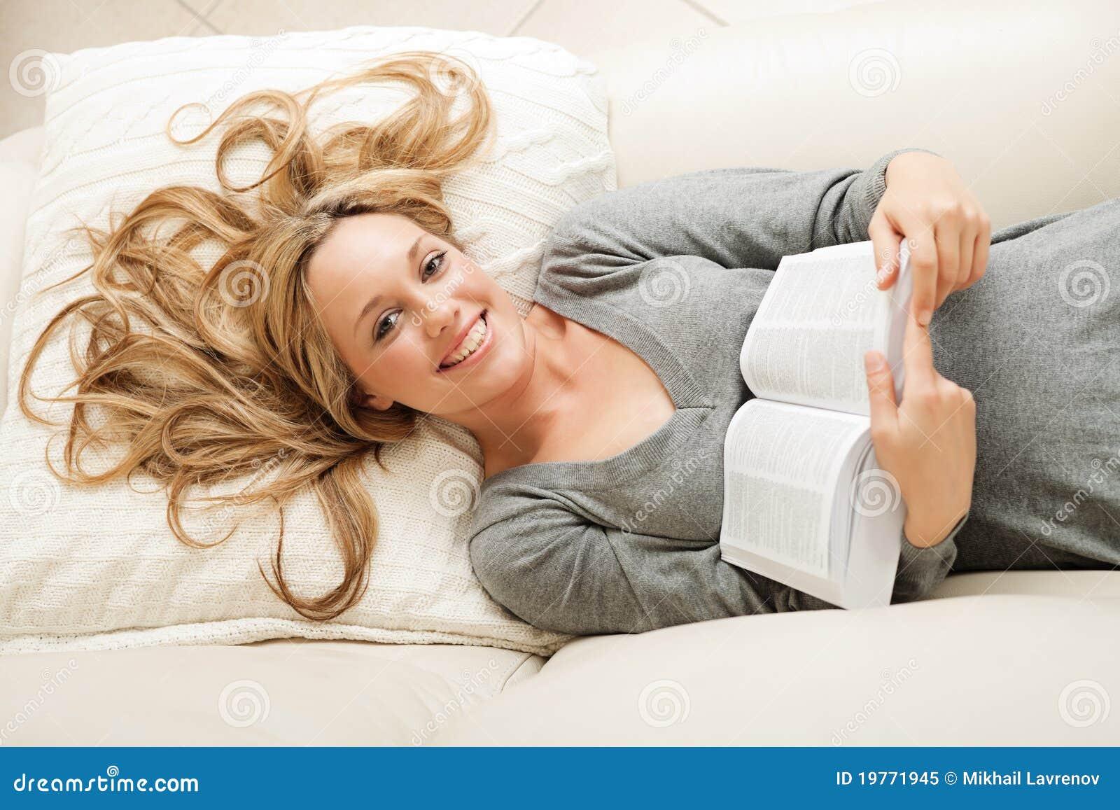 Gelukkige jonge vrouw die met boek ligt