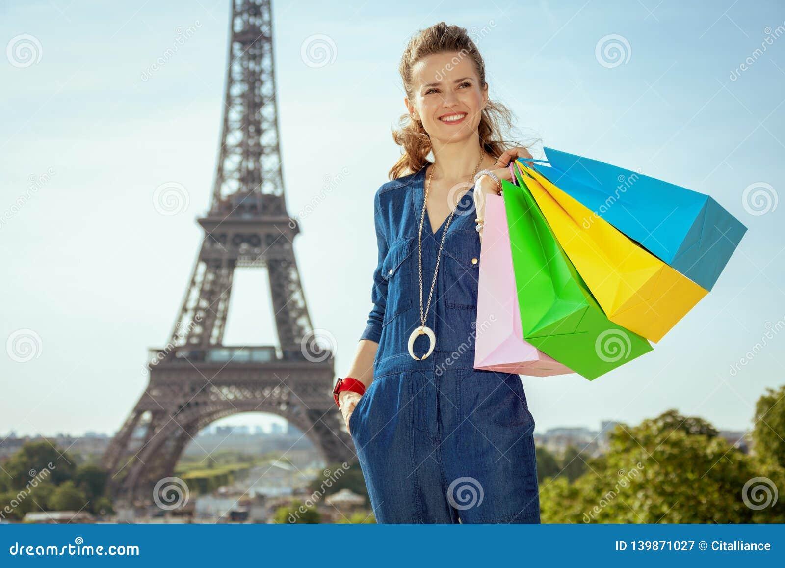 Gelukkige jonge vrouw die met het winkelen zakken afstand onderzoeken