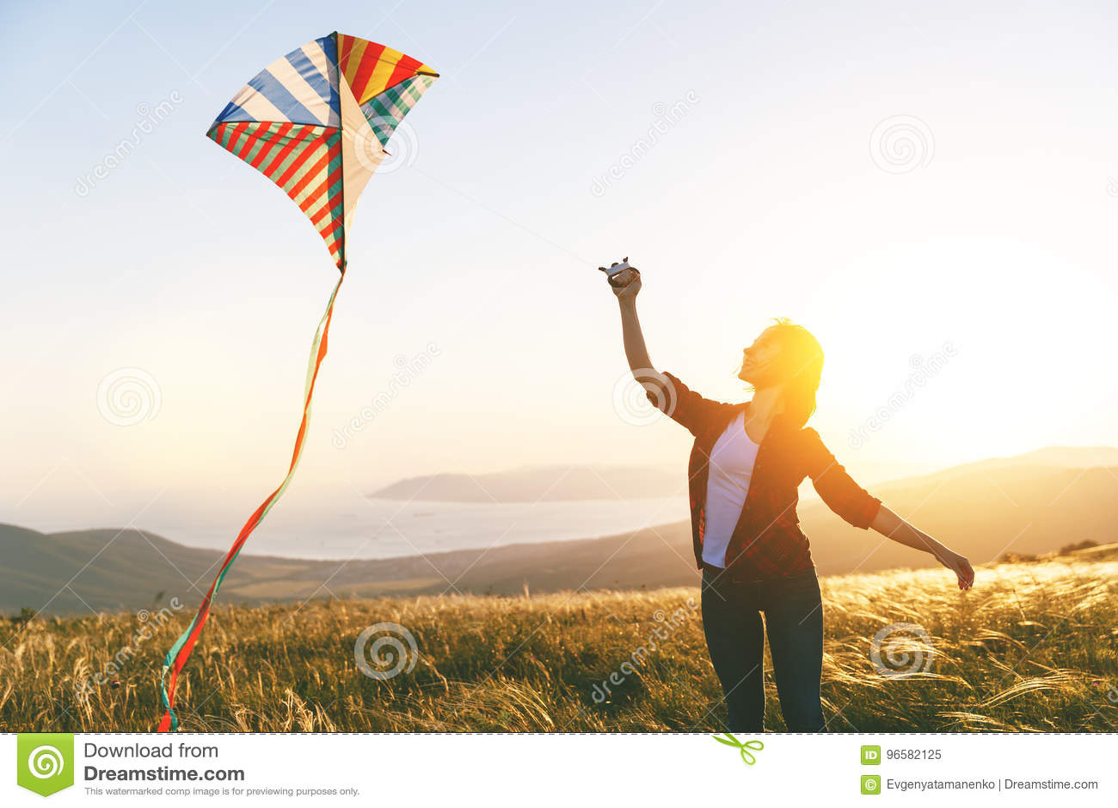 Gelukkige jonge vrouw die met vlieger op open plek bij zonsondergang in de zomer lopen