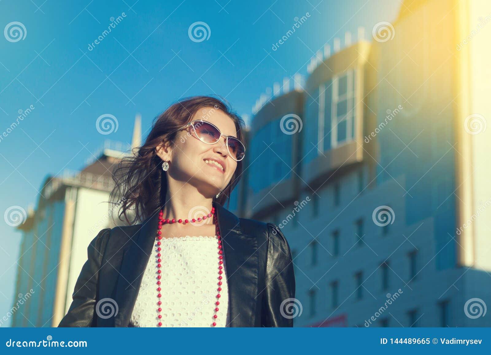 Gelukkige jonge vrouw die op een stadsstraat lopen