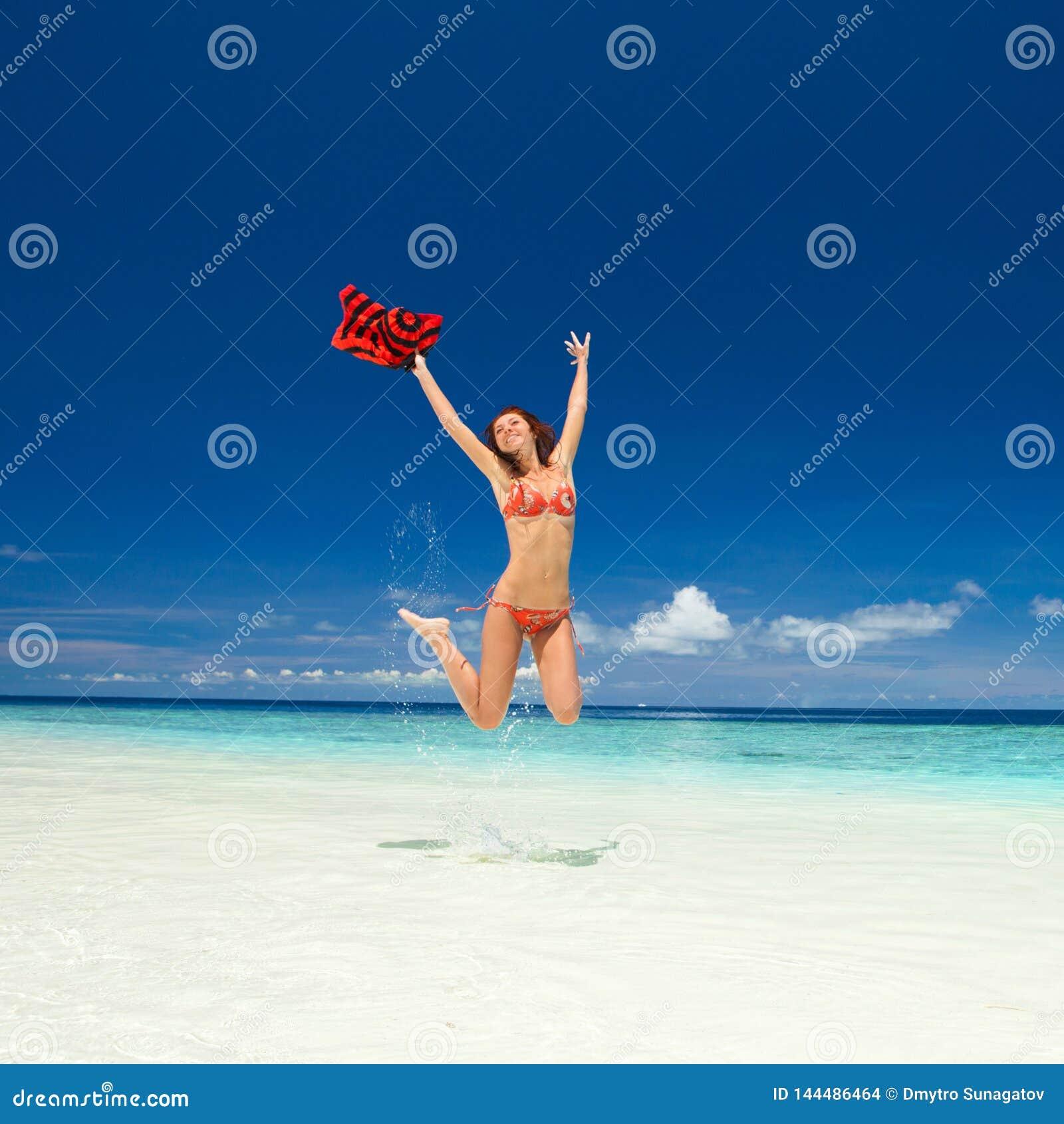 Gelukkige jonge vrouw die op het strand springt Gelukkige Levensstijl Wit zand, blauwe hemel en kristaloverzees van tropisch stra