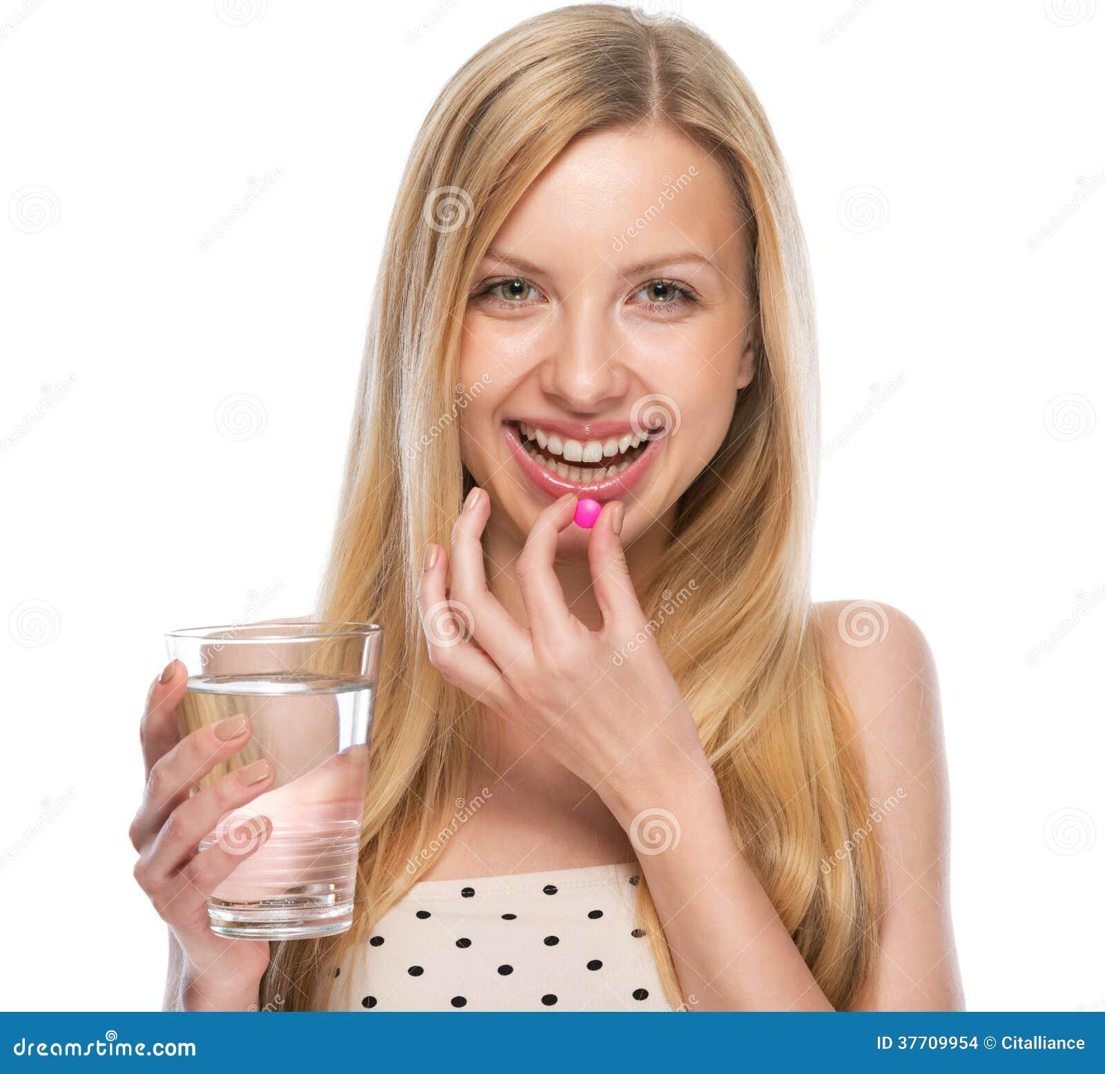 Gelukkige jonge vrouw die pil eten