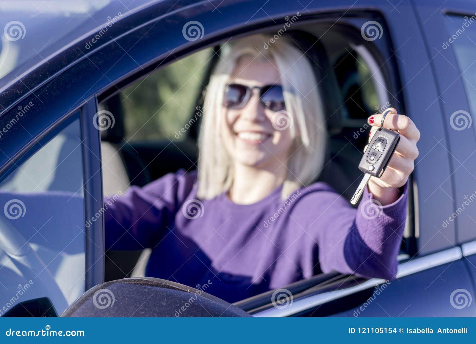 Gelukkige jonge vrouw die sleutels van haar eerste auto tonen - zijaanzicht